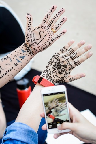 Photo: Two hands with henna pictures and words