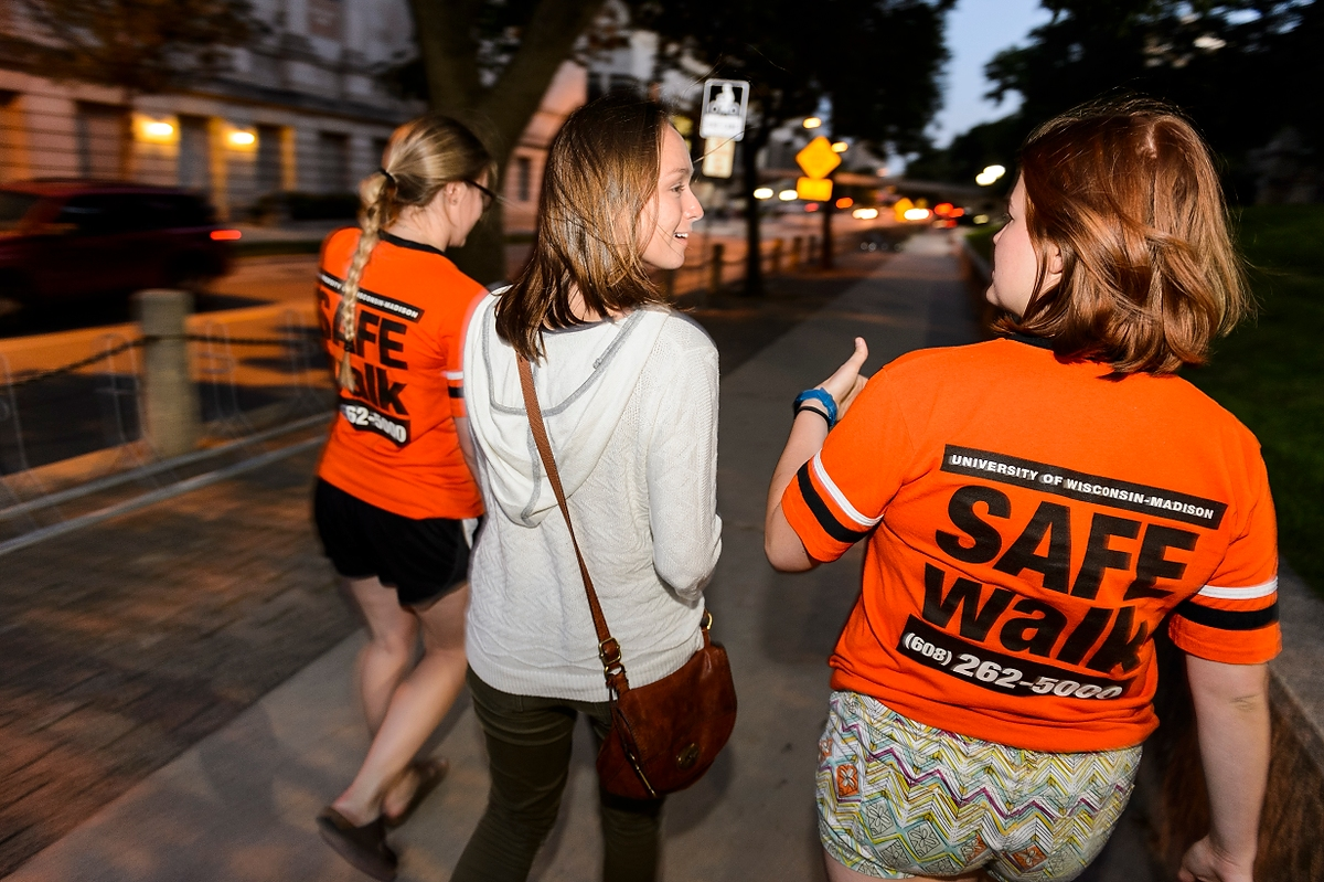 SAFEwalk staff members escort a UW–Madison student. SAFEwalk is a free campus service that provides trained, two-person walking escorts throughout the main campus.
