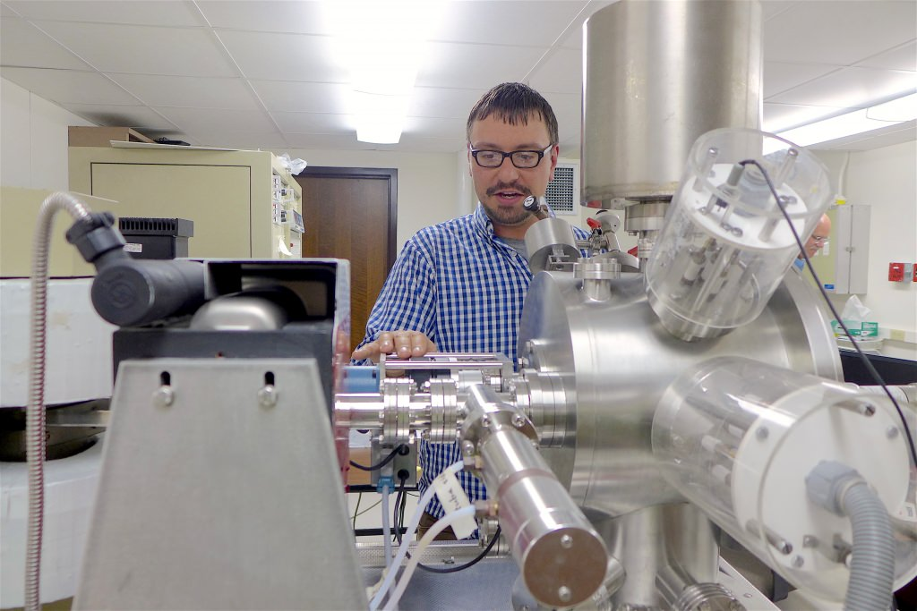 Aaron Satkoski, a scientist in the Department of Geoscience at UW–Madison, with the mass spectrometer used to measure isotopes in rocks from South Africa.