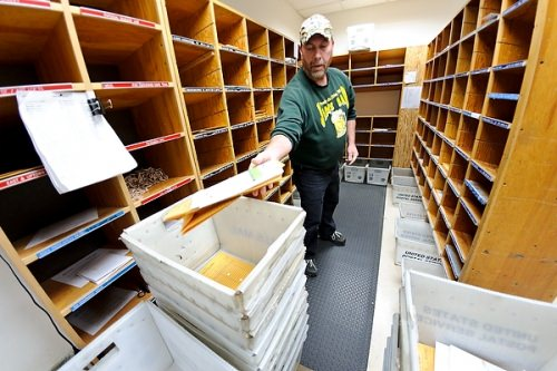 An employee places sorted mail into cartons to be loaded into delivery vehicles at the Campus Mail sorting facility at 45 N. Charter St.