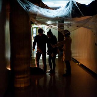 Participants navigate a dark hallway.