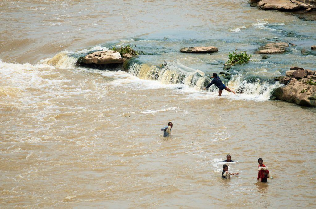Photo: Fishermen casting nets in river