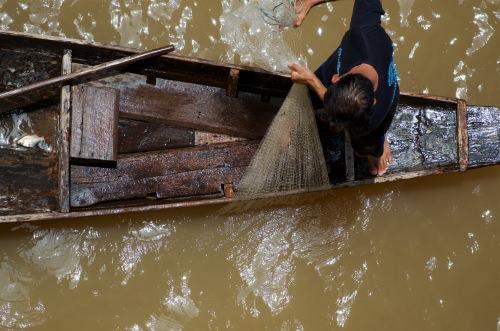 Photo: Man on boat pulling up fishing net