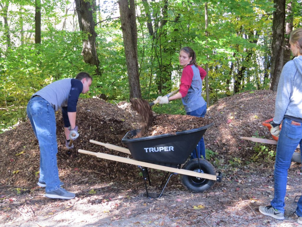 Midshipmen Nicholas Iacovo and Maren Kirkland load up mulch to repair the well-worn trails.
