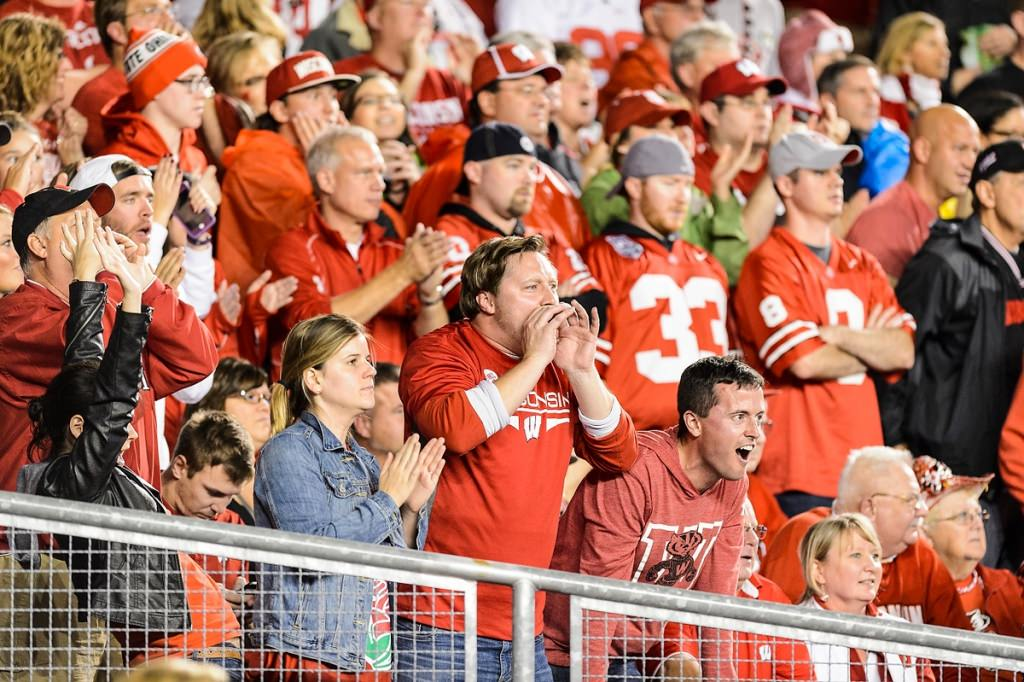 Badger fans cheer as the Wisconsin Badgers play the first half of a night football game against the Ohio State University (OSU) Buckeyes.