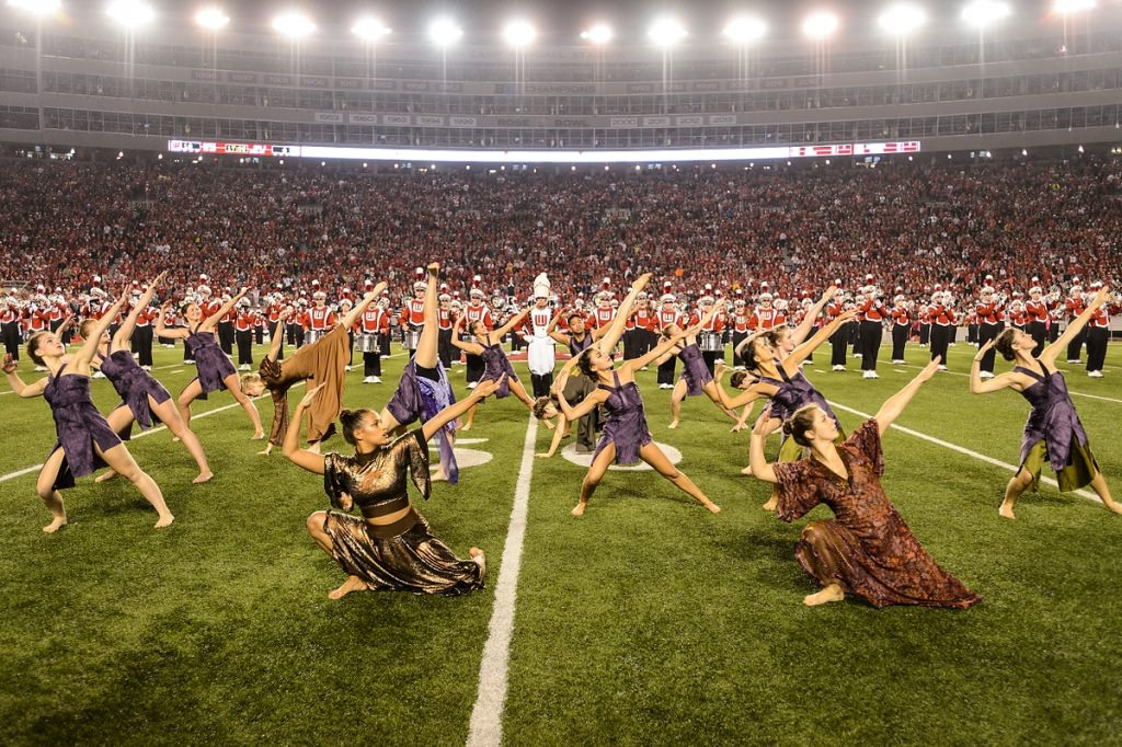 Members of the UW Dance Program perform a rendition of The Lion King with the UW Marching Band during halftime.