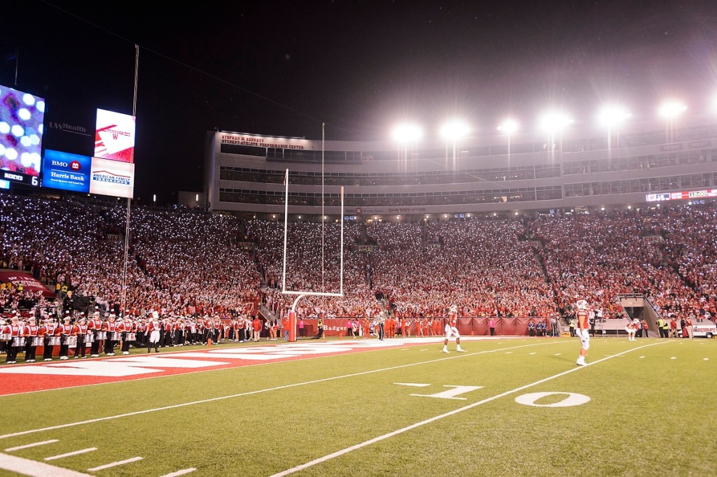 Badger fans shine their smartphone lights as the Wisconsin Badgers come out for the second half of play in a night football game against the Ohio State University (OSU) Buckeyes at Camp Randall Stadium.