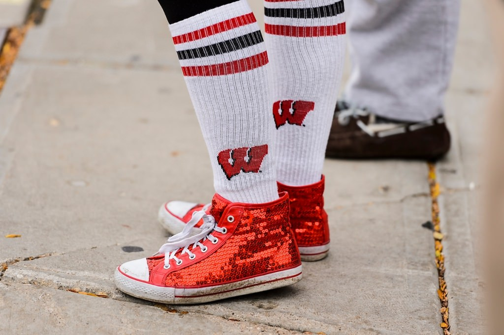Sporting Wisconsin-themed socks and bedazzled red shoes, a Badger fan walks to Camp Randall Stadium.