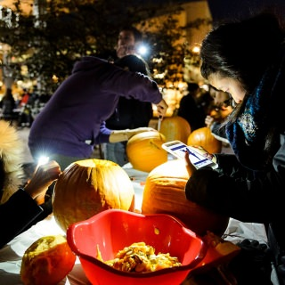 Cellphones provide light and the benefit of seeing potential patterns during pumpkin carving at Union South.