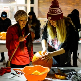 Students learned the technique for night-time carving: One holds a cellphone light and the other carves the pumpkin.