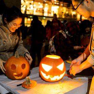 Ming Zhou, right, a graduate student from China studying electrical engineering, and his wife, Qing Chen, carve pumpkins.