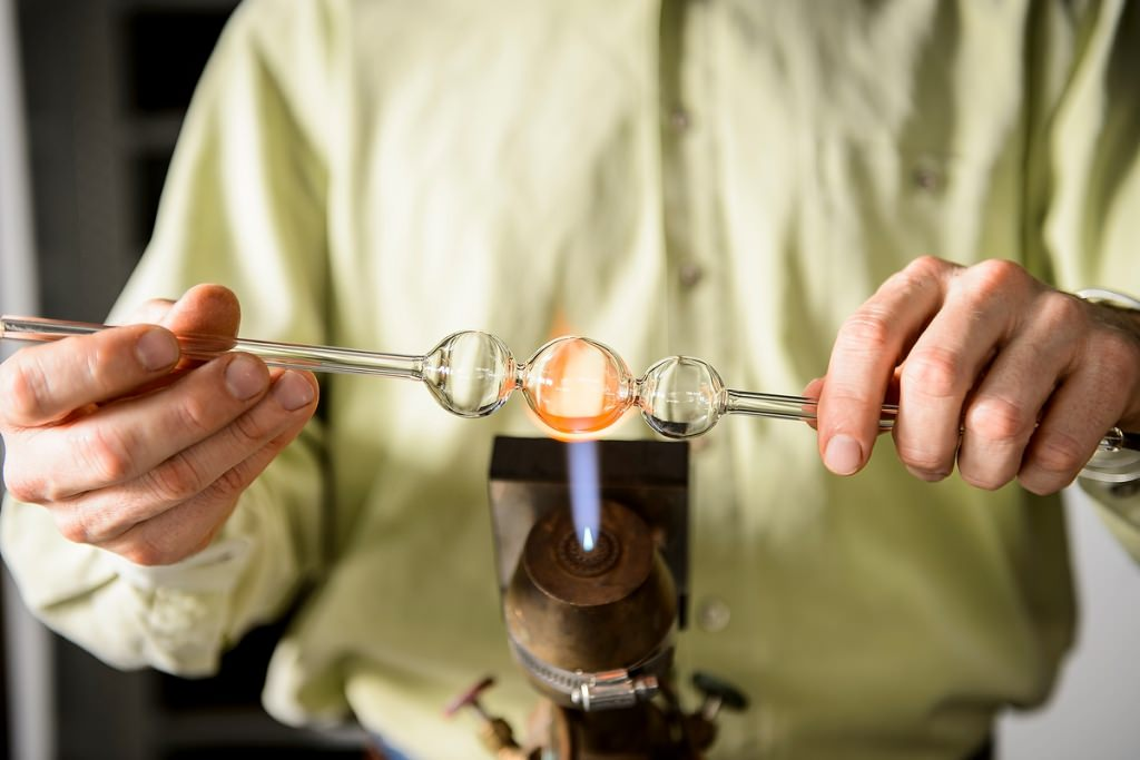 Fired up: The chemistry department's master glassblower, Tracy Drier, employs a blowtorch to create a highly specialized lab instrument. Drier was one of nine 2016 Academic Staff Excellence Award recipients.