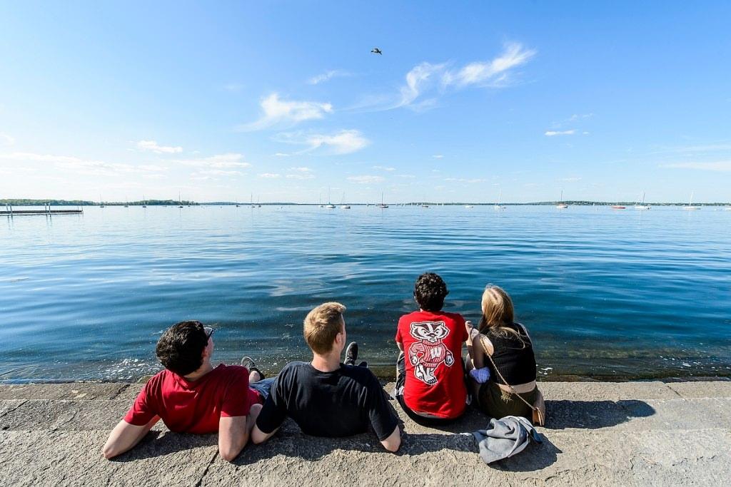 Photo: Students sitting along lake