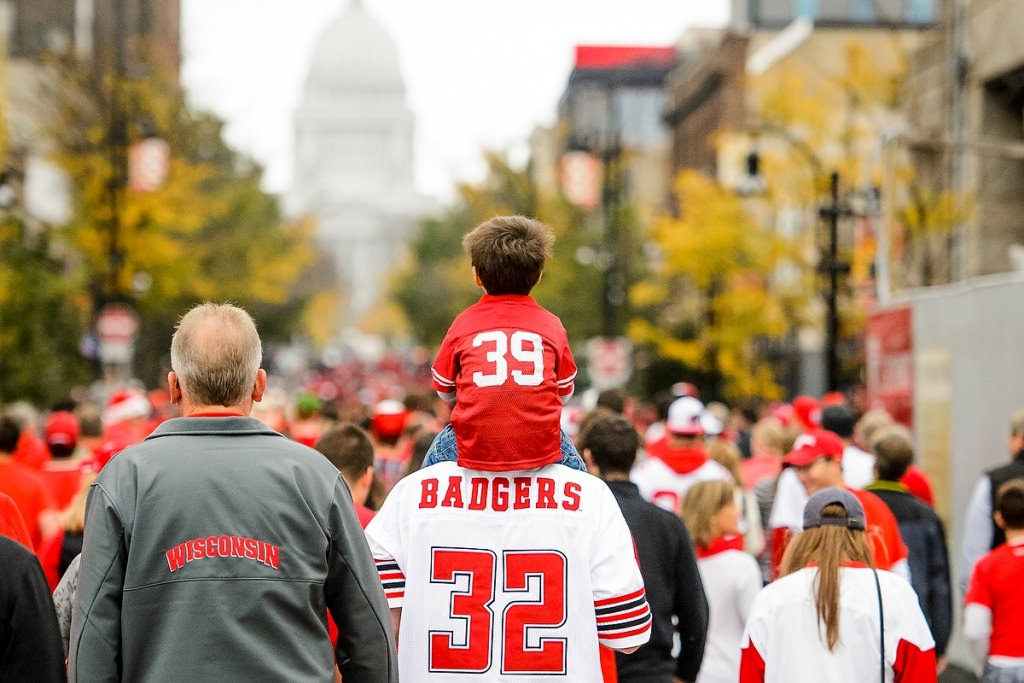 Photo: Child in Badger jersey riding on adult's shoulders