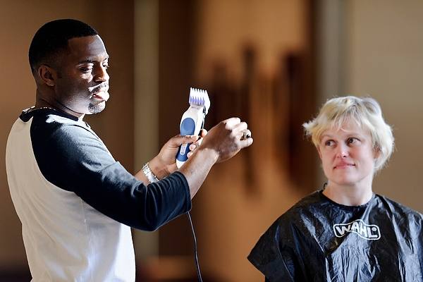 Photo: Artist — and barber — Faisal Abdu'Allah talks about his work while cutting the hair of volunteer Alison Jones Chaim during a live salon held in the Chazen Museum of Art lobby while he was serving as the Arts Institute's Spring 2013 Interdisciplinary Artist in Residence.
