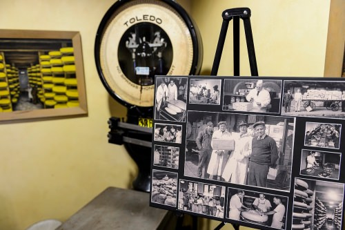 Pictured at center holding a parcel of cheese, company founder Ray Kubly Sr., is featured in a collage of historical company photos and artifacts on display at Colony Brands.