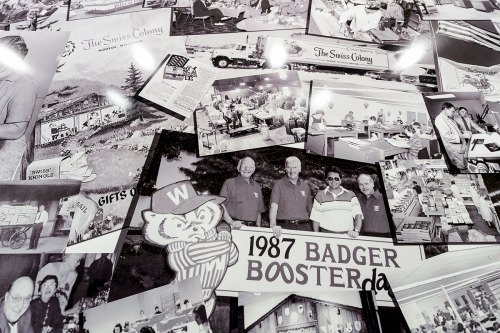 Pat Kubly, chairman of the board of Colony Brands and son of Ray Kubly, Sr., is pictured standing with his hand above the date 1987 in a collage of historical company photos on display at Colony Brands.