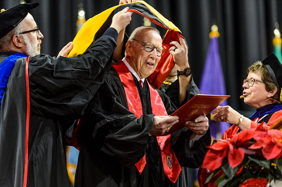 Capt. James A. Lovell Jr., is hooded as he receives an honorary degree from UW–Madison Chancellor Rebecca M. Blank during UW–Madison's winter commencement ceremony at the Kohl Center at the University of Wisconsin–Madison on Dec. 18, 2016. Lovell later spoke and delivered the charge to graduates. The indoor graduation was attended by approximately 1,000 bachelor's and master's degree candidates, plus their guests. (Photo by Jeff Miller/UW-Madison)