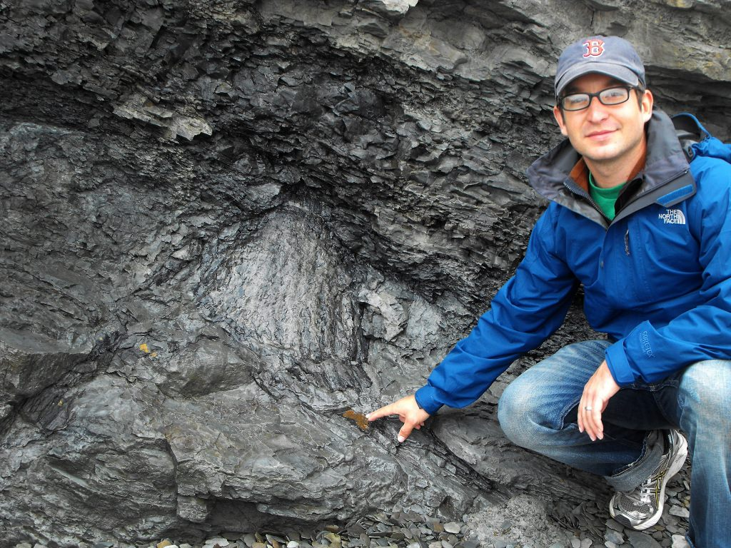 Photo: Jon Husson pointing to fossil
