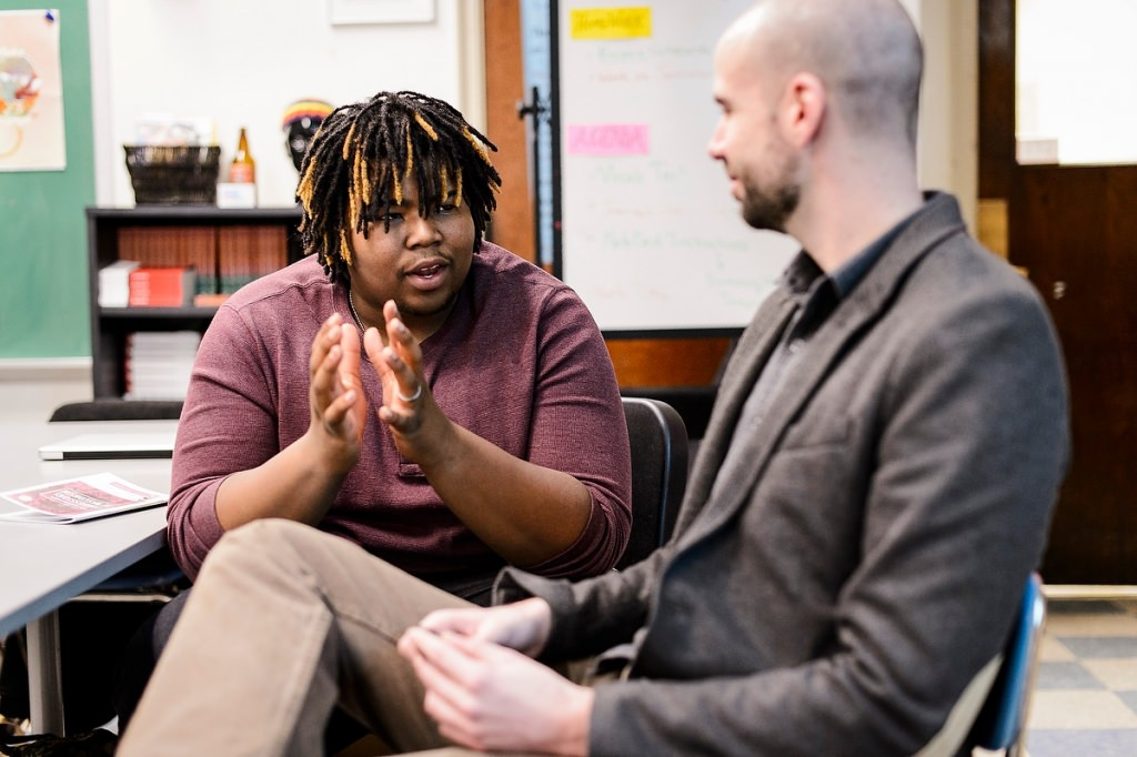 Photo: Manuel Herrero-Puertas, right, program coordinator for the Great World Texts in Wisconsin, talks with Shorewood High School student Richard Lafford, Great World Texts is an outreach program that connects scholars at UW–Madison with high school teachers and students across the state through reading and discussing a classic piece of world literature.