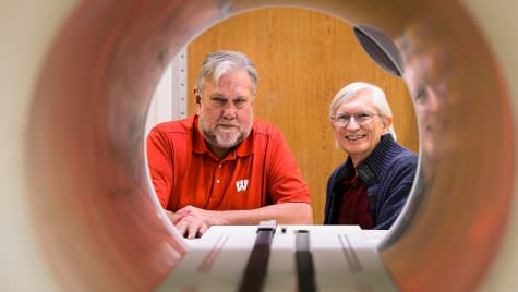 Frank Rath, left, a faculty associate in the College of Engineering, and Bruce Thomadsen, professor of medical physics, are pictured looking through the opening of a piece of radiotherapy treatment equipment at the Carbone Cancer Center. Thomadsen helped found the Center for the Assessment of Radiological Science as a way to help monitor and improve incidents of radiation-treatment safety in health care.