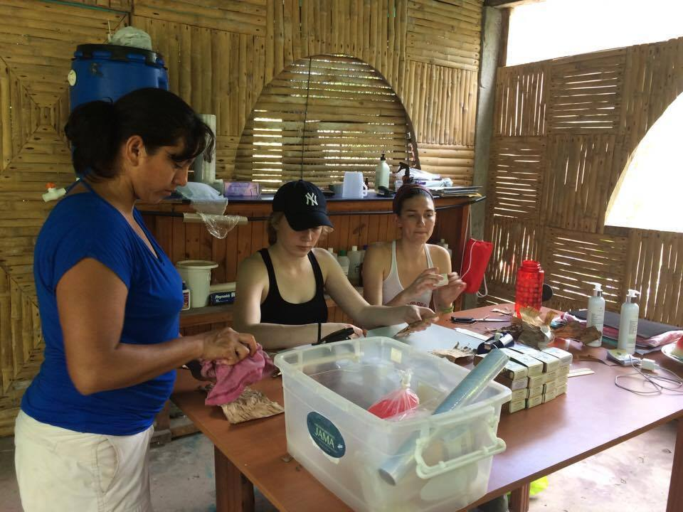 WWBM student director Jen Wagman, center, and operations coordinator Sophia Goldschmidt, right , work with local women to make necklaces during a trip to a Belina Jabon in Ecuador.