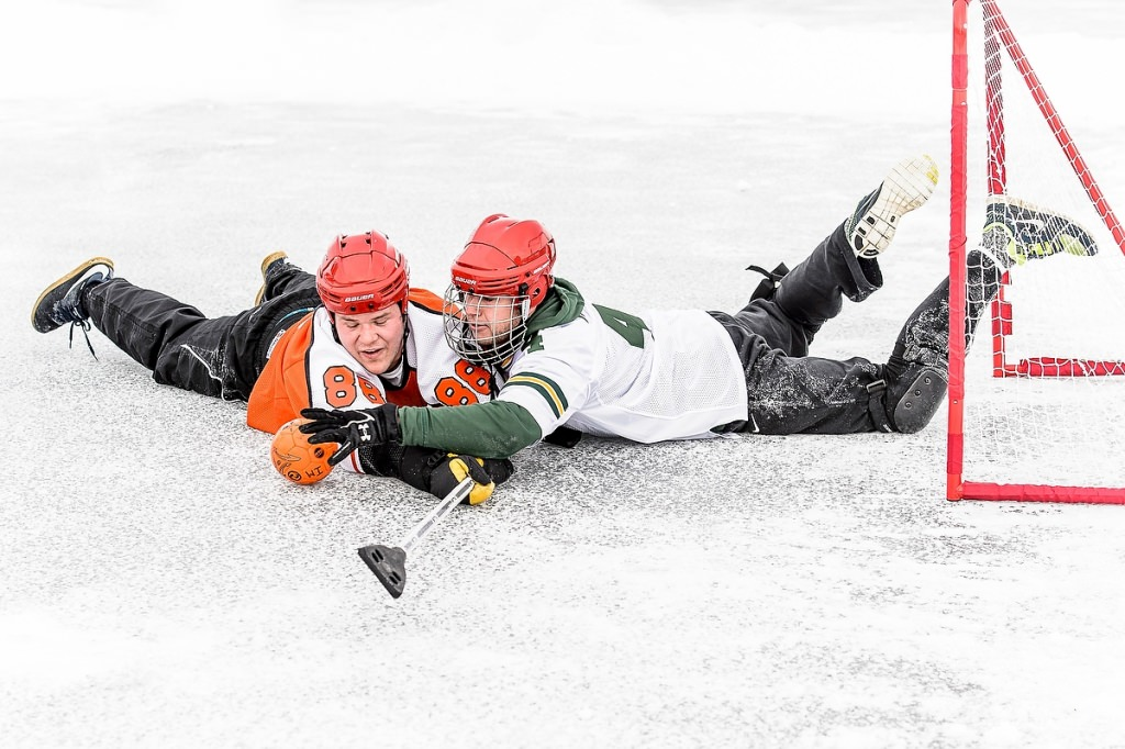 Joey Horan, left, and James Oelke, right, fight for possession during the broomball tournament.