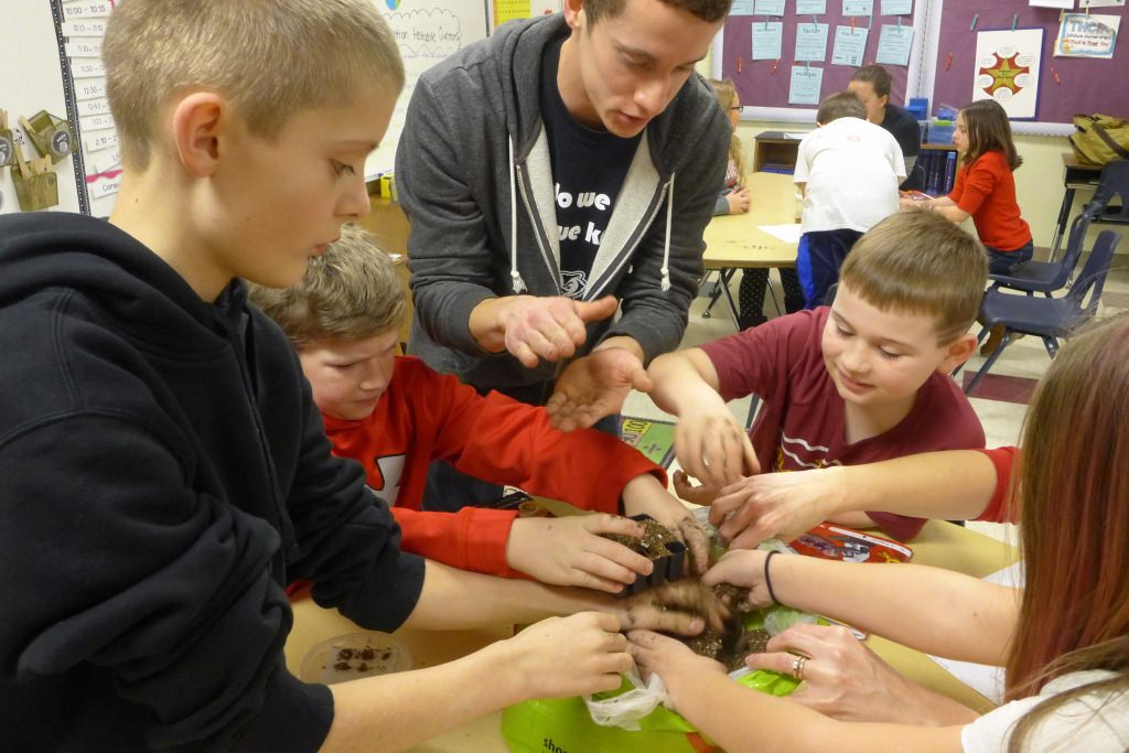 Patrick O'Grady, a Biocore alumnus, superintends as students place soil in a container before planting seeds. Using Wisconsin Fast Plants, three recent alumni of the Biocore learning community at UW–Madison participated in an inquiry-based class at Mazomanie Elementary School on Jan. 30.