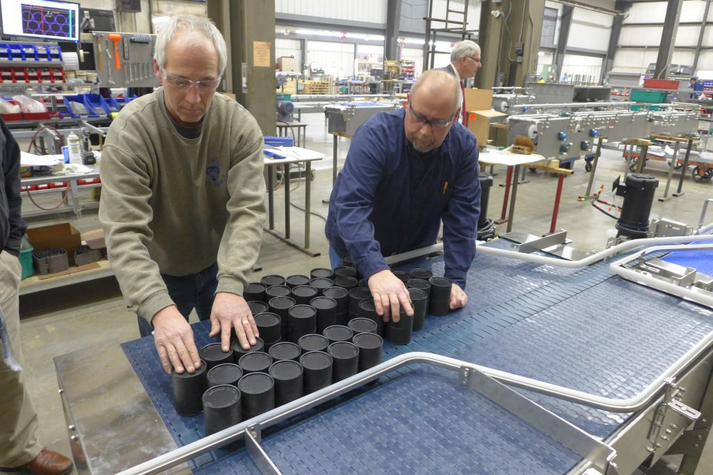 Photo: Men looking at containers on conveyor belt