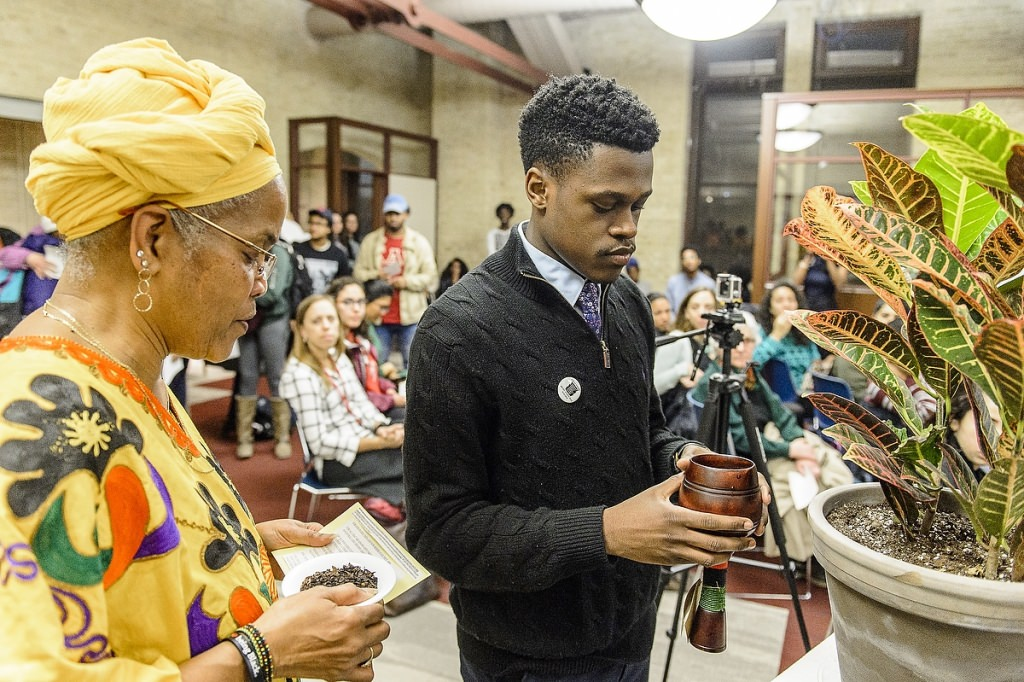 Hazel Symonette, left, program development and assessment specialist in the Division of Student Life, and Marquise Mays (right), chair of the Wisconsin Black Student Union, perform a libation pouring ritual in memory of those who have passed on during a dedication and libation ceremony for the new Black Cultural Center at the Red Gym.