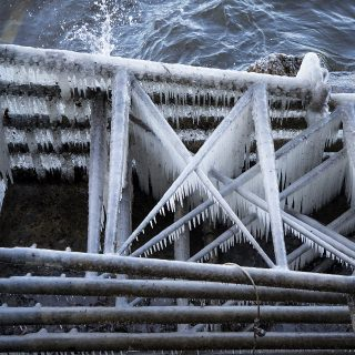 Stacked structures for the limnology pier collects icicles as the strong wind pushes Lake Mendota water to the shore.