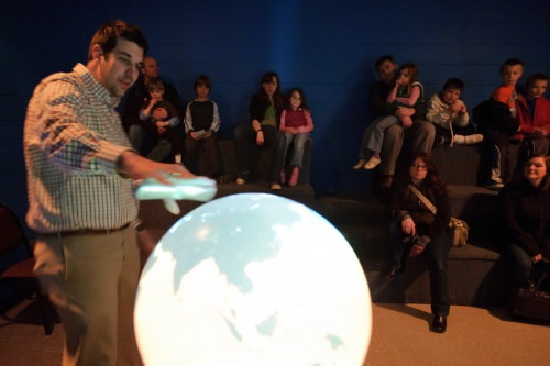 Referencing a 3-D weather globe displaying real-time and recorded satellite imagery, an outreach specialist with the Space Science and Engineering Center (SSEC), describes weather patterns on Earth to a group of families and visitors participating in Science Expeditions in 2011.