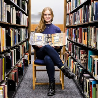 Undergraduate student Elise Schimke sits with her photo book,