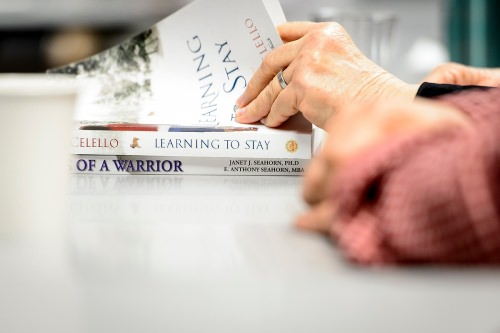 A participant searches for a passage of text during a discussion session held by the Warrior Book Club.