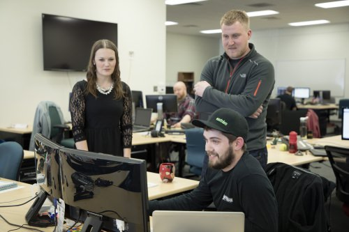 "At Foot Locker's offices in Wausau, ""product owner"" Jacklyn Cummins and ""scrum master"" John Hocker discuss a fine point of software development with ""product manager"" Jordan Meyer."