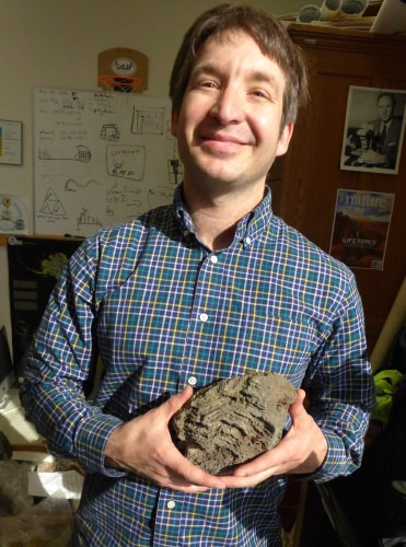 John Husson, a post-doctoral researcher working with Shanan Peters, holds a stromatolite, a biologically based structure that was much more common early in Earth history.
