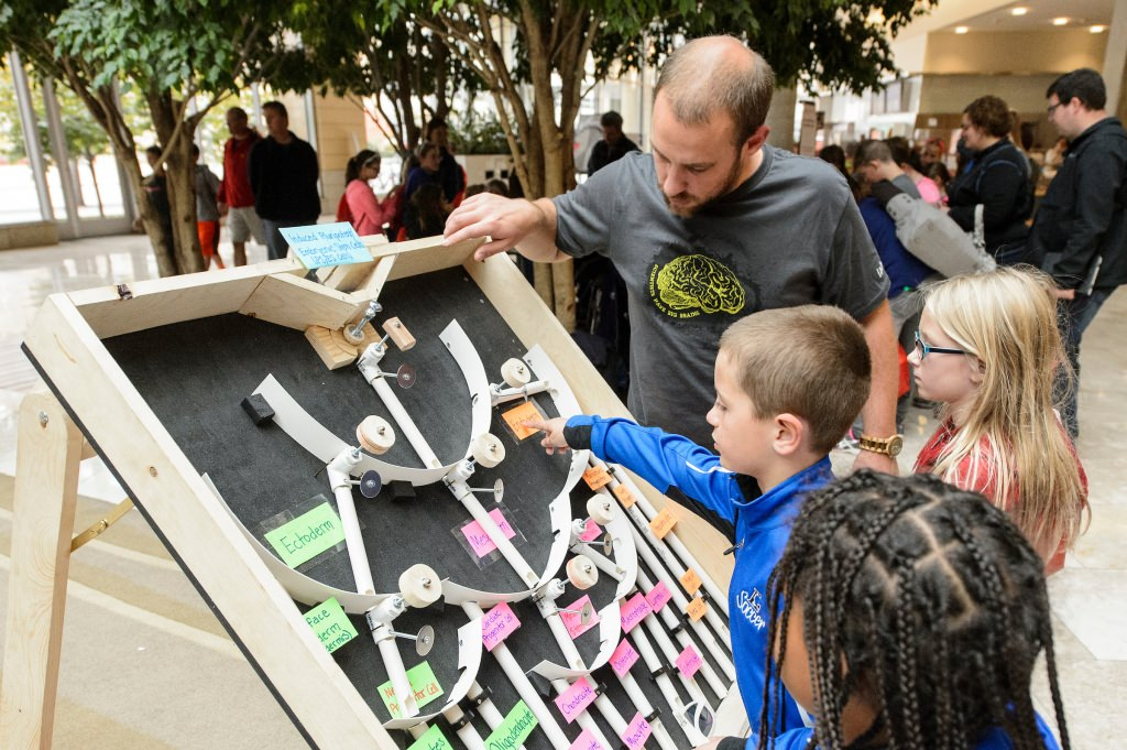 """Josh Knackert (left), graduate student in biochemistry, works with young participants at a """"Choose Your Own Fate"""" info booth at the Wisconsin Science Festival, a statewide celebration of curiosity and science exploration from Oct. 22-25, 2015. (Photo by Bryce Richter / UW–Madison)"""