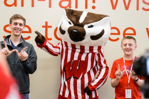 Undergraduate Jacob Lindemann and his brother Adam, 13, of Manitowoc, pose for a photo with mascot Bucky Badger at Union South during Sibs Day activities.