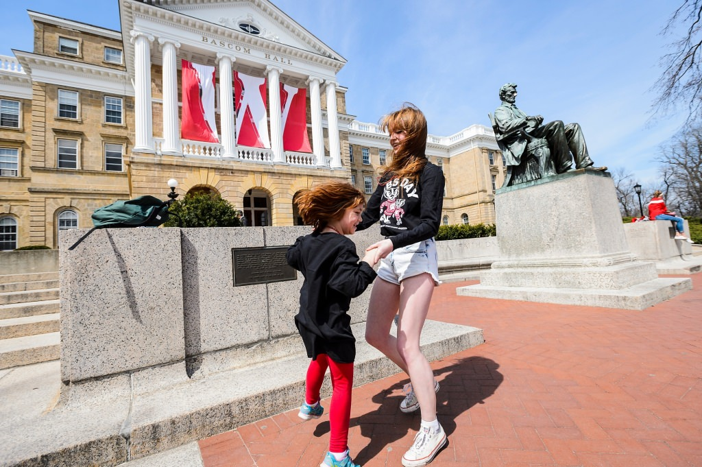 Undergraduate Celeste Huff and his sister Melina, 6, of Wisconsin Rapids, Wis., stop to dance a polka by Bascom Hall and the Abraham Lincoln statue as they participate in campus scavenger hunt, part of Siblings Day at the University of Wisconsin–Madison on April 8.