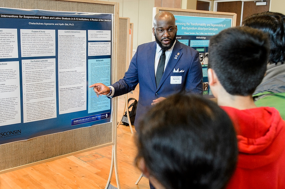 Chetachukwu Agwoeme discusses his research at the Undergraduate Symposium on April 13. A record 683 students took part.