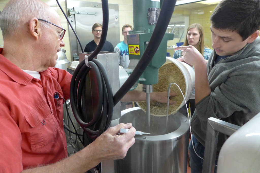 Instructor Hans Zoerb (left) and student Leo Gallagher pour malted barley into the mash tun at the UW–Madison Craft Brewery in Babcock Hall at UW–Madison, starting the brewing process for one of the six beers that were considered for production this spring.