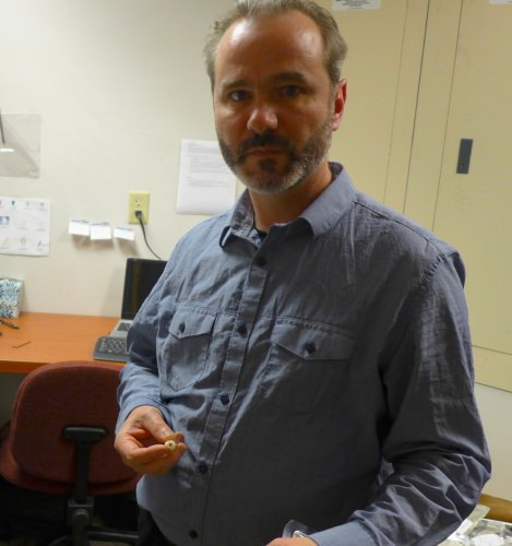 Dan Butz, a scientist at Isomark, a UW–Madison spinoff, holds a fitting that connects the sample container to Isomark's analytical instrument.