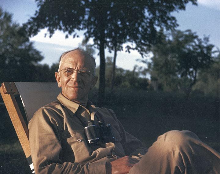 Photo: Aldo Leopold sitting outdoors with binoculars