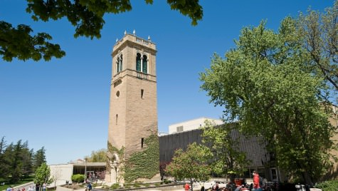 Trees and pedestrians frame a view of the Carillon Tower in front of the Sewell Social Sciences Building.