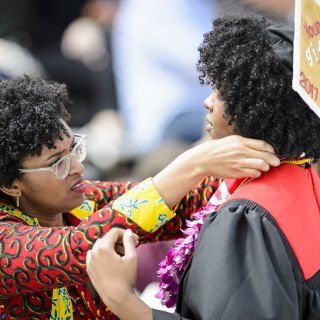 A graduate gets help with her gown.