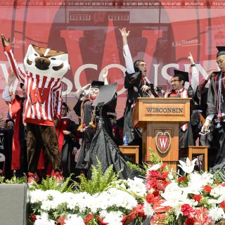 Bucky Badger joins the commencement stage party for
