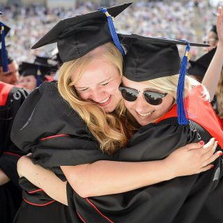 Two graduates share their emotions at the conclusion of Saturday's ceremony at Camp Randall.