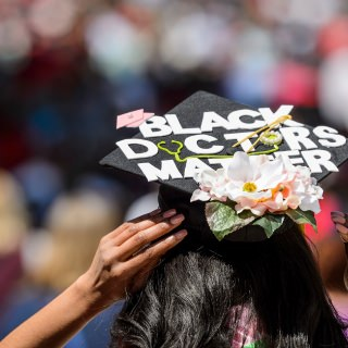 Morgan Hill adjusts her mortarboard – decorated with the message,