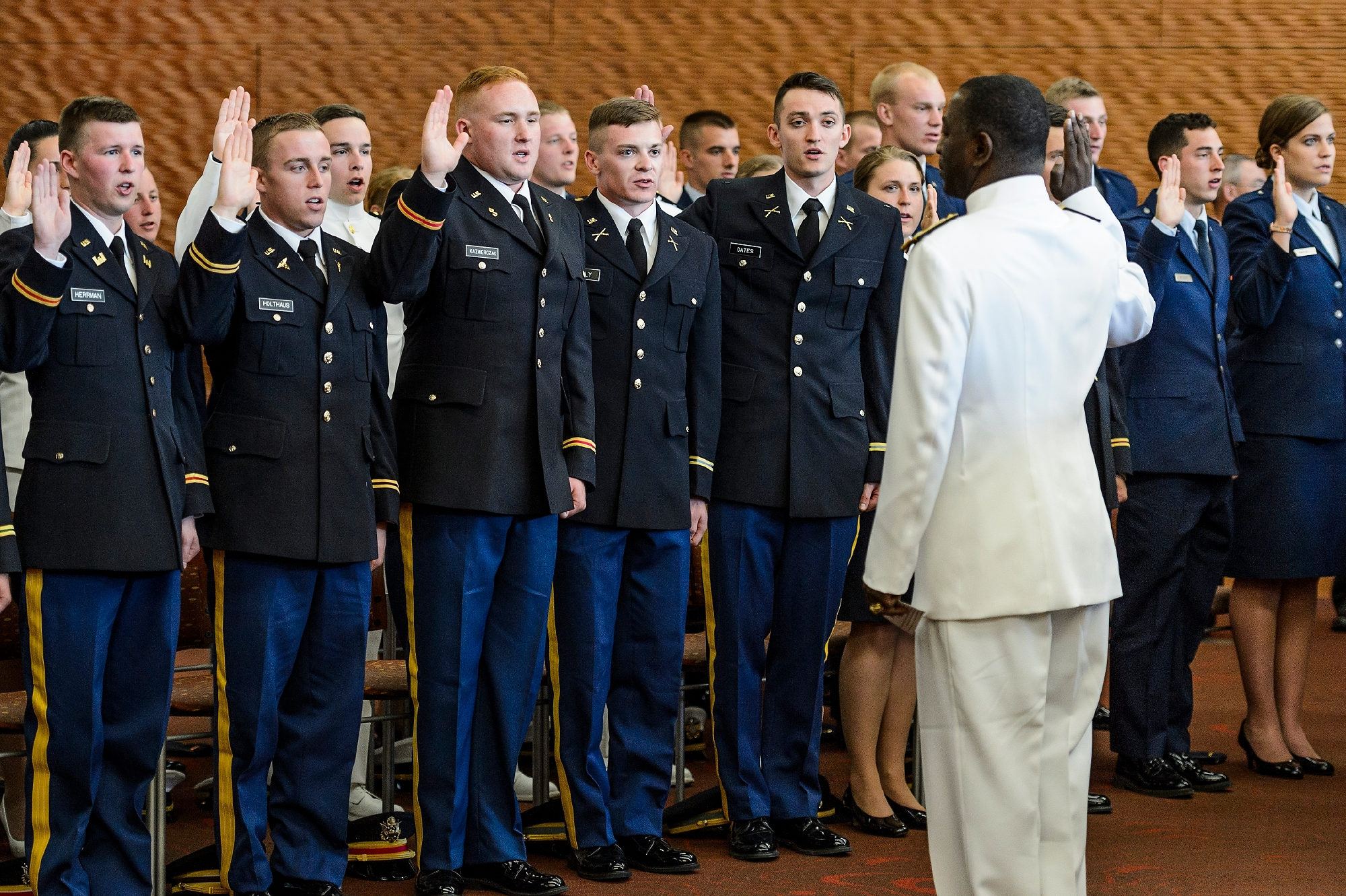 Members of UW–Madison's Army, Navy and Air Force ROTC units take the oath of office, led by Rear Admiral Stephen C. Evans, at right, during an officer commissioning ceremony at Gordon Dining and Event Center on May 13.