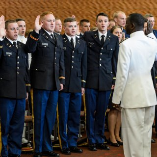 Led by Rear Adm. Stephen C. Evans, commander of the U.S. Naval Service Training Command, right, members of UW-Madison's Army, Navy and Air Force Reserve Officer Training Corps take the oath of office during a ceremony Saturday. The event formally recognized 32 graduates from UW-Madison as officers in the military.